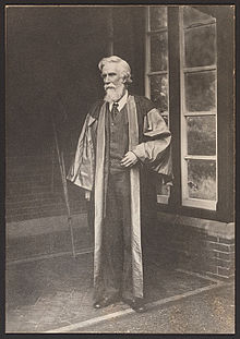 A bearded Albert Venn Dicey stands in a suit and academic robes facing left