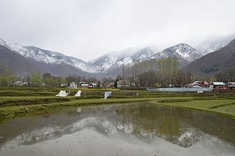Aragam - The view of Aragam village with snow clad mountains in backdrop.