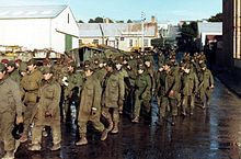 About forty soldiers wearing olive-green jackets and pants march down a wet urban street. They are guarded by three commandos with green berets and camouflage pattern jackets. In the background are paratroopers in similar camouflage jackets and maroon berets.