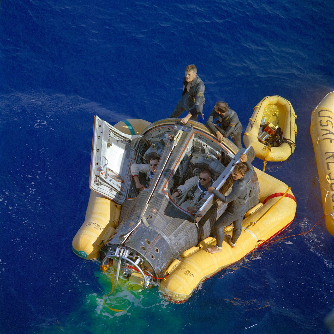 A dark gray Gemini capsule floats horizontally in blue water. It is supported by a yellow flotation collar. The hatches are open and the astronauts are visible sitting in their places wearing sunglasses. They are being assisted by three recovery crew in dark gray wetsuits.
