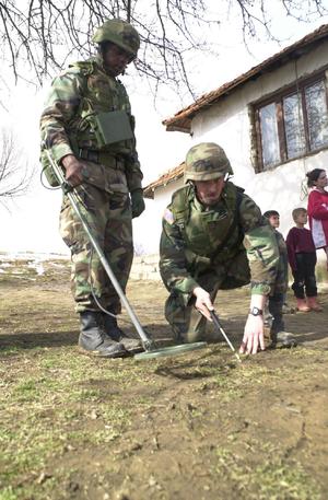 Metal detector - U.S. Army soldiers use a metal detector in 2002.