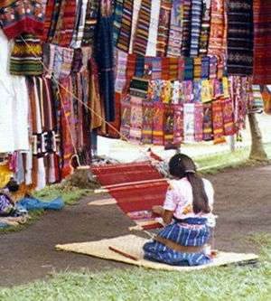 Textiles of Oaxaca - A woman from Guatemala works on a backstrap loom, in Mesoamerican tradition.