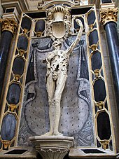 Limestone statue of a putrefied and skinless corpse which looks upwards at his outstretched left hand.