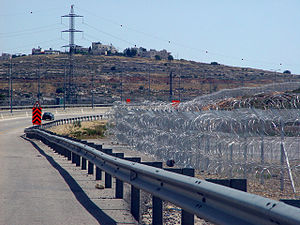 Route 443 (Israel) - Route 443 near Giv'at Ze'ev Junction, with pyramid-shaped stacks of barbed wire forming a section of the Israeli West Bank barrier