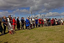A line of people in mediaeval dress and armour, several with weapons, stand under a cloudy sky.