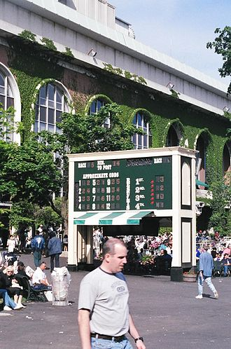 Belmont Park - The elegant, ivy-framed arched windows of the Belmont grandstand lurk behind the tote board in the backyard in this 1999 photo; the tote board has changed to a digital tote and TV display since then. The current grandstand, Thoroughbred racing's largest, was completed in 1968 after five years of renovations to the Belmont complex.