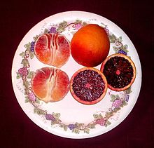 A plate showing three blood oranges: one whole, one peeled, and one sliced in half