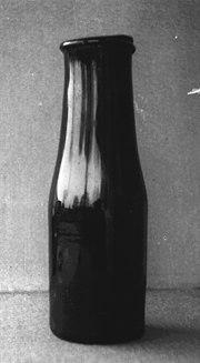 Photo en noir et blanc d'une bouteille, en verre très sombre, dont le goulot est à peine plus étroit que le corps et se termine par un rebord saillant à l'extérieur.