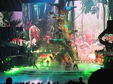 A blond woman female performer wearing a black outfit on top of a giant tree, while other people look at her.