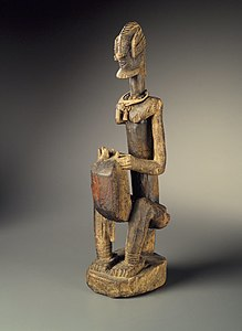 A wooden sculpture of a man seated on a low stool, playing a kora which rests on and slightly between his knees. The figure is stylized, with an elaborate hairstyle, the kora body slightly boxy.