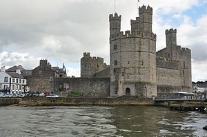 Caernarfon Castle - Caernarfon Castle from the west. The town's walls, which were mostly complete by 1285, join with the castle and continue off to the left of the photo.
