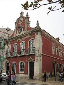 Former town municipal hall on Praça da República. Two stories. Dark pink. Clock atop building.