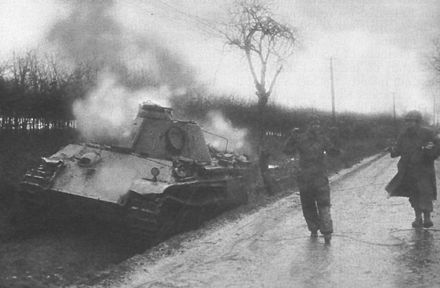 An American soldier escorts a German crewman from his wrecked Panther tank during the Battle of Elsenborn Ridge. Captured German Panther tank crewman 1944.jpg