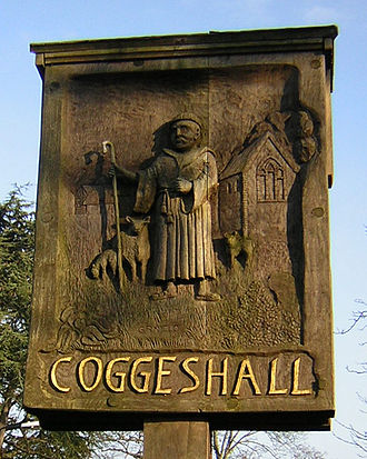Coggeshall - The town's sign depicts a Cistercian farming sheep at the abbey. On the other side is a weaver by his loom.