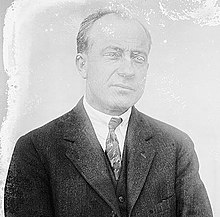 A man with graying, receding hair wearing a dark jacket, patterned tie and white shirt