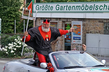 Part of the crowd during most days of the Tour is Didi Senft who, in a red devil costume, has been the Tour devil since 1993. Didi Senft-Einzelzeitfahren-Deutschlandtour 2005.jpg