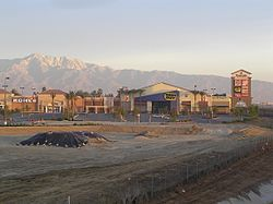 Eastvale Gateway - The main retail center for Eastvale, located at Interstate 15 off the Limonite exit.  The San Gabriel Mountains can be seen in the background.  In the foreground, construction of a stadium movie theater in the front.