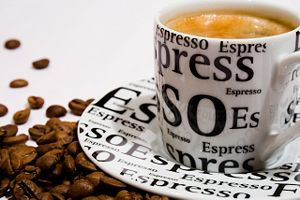 A cup of Espresso and coffee beans.