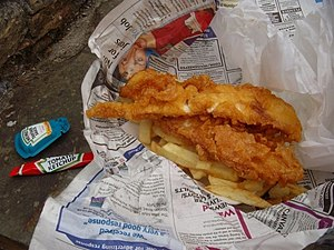 Disposable food packaging - Fish and Chips: wrapped in wax paper then with used newspaper, packets of condiments