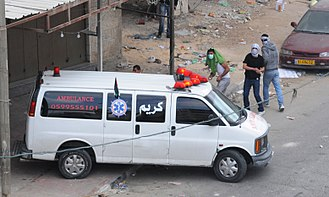 Palestinian stone-throwing - Palestinians throwing stones from the cover of an ambulance during a riot in Qalandiya.