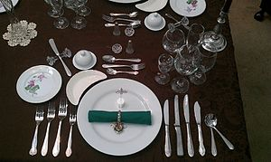 Cutlery - A table setting for an eight-course meal. It includes a butter spreader resting on a crystal stand; a cocktail fork, soup spoon, dessert fork, dessert spoon and an ice cream fork, as well as separate knives and forks for fish, entrée, main course and salad