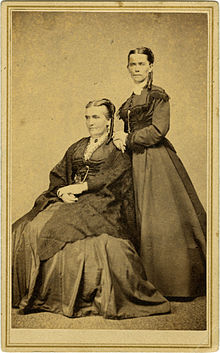 Two women—the older one seated and the younger one standing