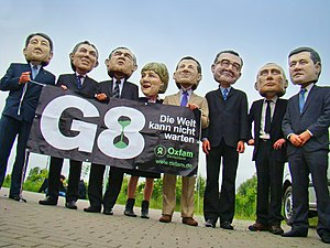 Oxfam protesters dressed as and wearing masks of the G8 leaders.