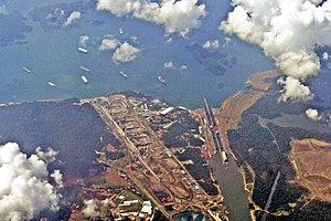 Panama Canal expansion project - Aerial view of Gatun Locks. On top, several vessels at the Gatun Lake waiting to cross the locks. At the bottom is exit canal to the Atlantic Ocean. At the left of the existing locks is the construction area for the new locks and water-saving chambers part of the Panama Canal expansion project.