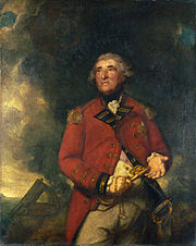 An portly English officer with a ruddy complexion and black eyebrows, stands in military dress against a background of smoke from a cannon. He holds a very large key in one hand and gestures with the other.