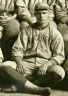 "A man, wearing a grey baseball cap, baseball jersey with ""MICHIGAN"" on the chest and dark baseball socks, sits on the floor with his legs crossed."