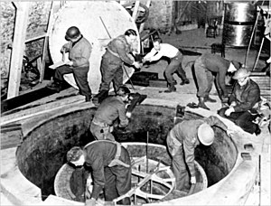 Seven men in uniforms, some wearing steel helmets, standing in and around a circular hole.