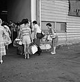 Groep passagiers met hun bagage vormen een wachtrij achter een hek bij het douan, Bestanddeelnr 255-2185.jpg