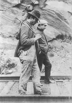 Two hobos walking along railroad tracks, after being put off a train - more than a century ago