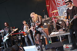 "A rock band performing live on stage. A poster with the words ""SPIN 20"" is in the background."