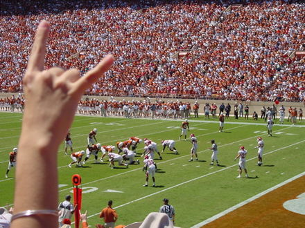 A fan displays the Hook 'em Horns during a Texas football game versus Arkansas. Hookemhorns.jpg