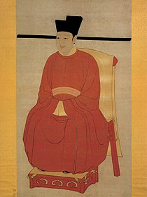 A painting of a young faced man in gold trimmed red robes, sitting on a throne made out of red wood covered in gold cloth.