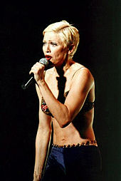 Madonna in short blonde hair, wearing a green bra and purple pants, singing to a microphone, held in her left hand.