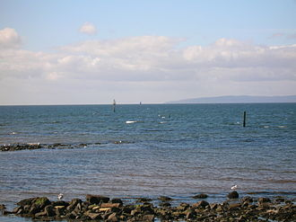 Boyd's Automatic tide signalling apparatus - The Irvine bar channel entrance with the Isle of Arran in the distance and one of the old harbour lights on the post to the left.