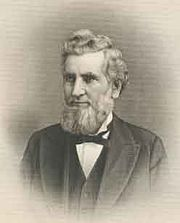 An older man, facing left, with curly, white hair and a beard. He is wearing a white shirt, black tie, and black jacket