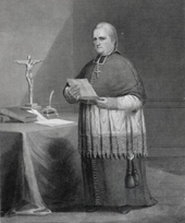 Black and white illustration of a man wearing a zucchetto, liturgical vestments, and a pectoral cross facing right, with a crucifix on a table to his right.