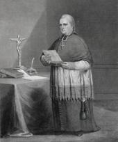 Sort og hvid illustration af en mand iført en zucchetto, liturgiske klæder og et brystkors mod højre med et krucifiks på et bord til højre for ham.