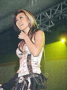 A woman is standing on stage. Her long hair has blonde highlights, and she is wearing a white corset-like shirt and a belt with many accessories attached to it.
