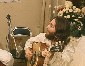 A man with long dark hair and a beard, wearing glasses and a white jacket, playing a guitar