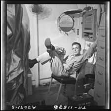 Lt. Wayne Miller relaxes in his quarters on the USS Ticonderoga (CV-14). - NARA - 520842.jpg
