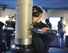 A young visitor looks through the WWII-era TANG periscope in MOHAI's Maritime Gallery