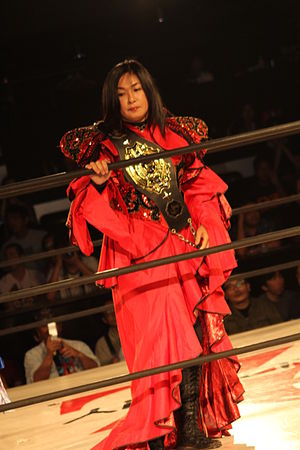 Manami Toyota - Toyota with an Oz Academy Tag Team Championship belt in July 2011