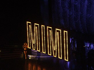 "Shake It Off (Mariah Carey song) - A still of Carey performing ""Shake It Off"" during The Adventures of Mimi Tour (2006). Carey is shown walking down the spiral staircase, onto the main stage, as the Broadway-styled 'MIMI' prop descend from the rafters."