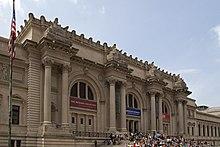 Uma fachada de pedra de vários andares muito ornamentada se eleva sobre degraus e uma praça à noite.
