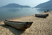 Two small dugout canoes on the shore of a lake