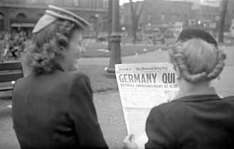"1945 in Canada - Two young women standing on Saint Catherine Street in Montreal, reading the front page of The Montreal Daily Star. The title ""Germany Quit"" announces the German surrender and the impending end of the World War II in Europe."